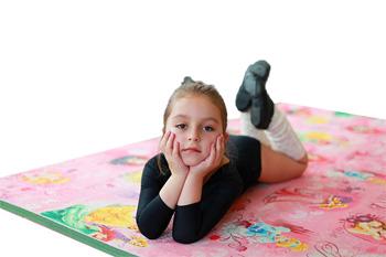 Девочка лежит на спортивном ролл-мате